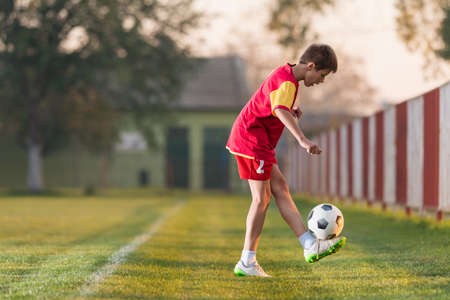 futbol soccer: Niño que juega al fútbol en un campo de fútbol Foto de archivo