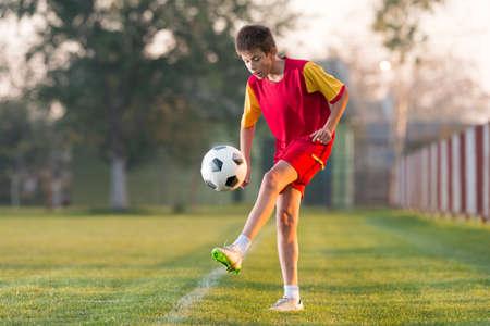 cancha de futbol: Niño que juega al fútbol en un campo de fútbol Foto de archivo