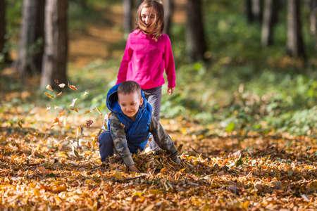 niños jugando en el parque: Niños jugando con las hojas de otoño caidas en parque