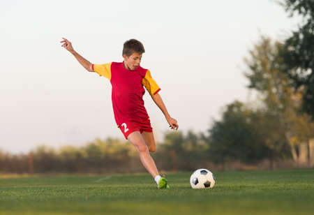elementary age boys: kid kicking a soccer ball on the field