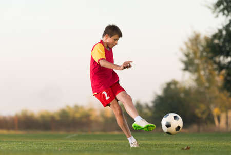 only boys: kid kicking a soccer ball on the field