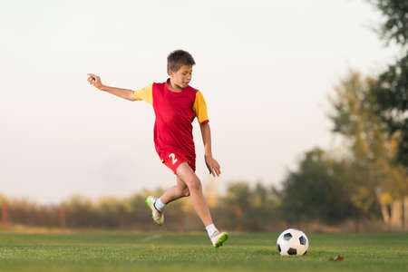 one boy only: kid kicking a soccer ball on the field