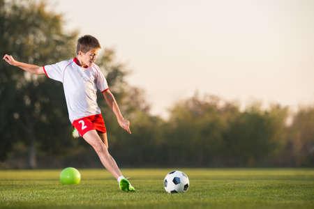 balones deportivos: chico patear un balón de fútbol en el campo