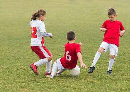 kids kicking football on the sports field