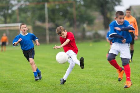 elementary age boys: boy kicking football on the sports field Stock Photo