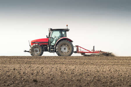 plough machine: Tractor preparing land for sowing Stock Photo