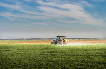 Traktor Weizenfeld Besprühen mit Sprayer Standard-Bild - 49304596