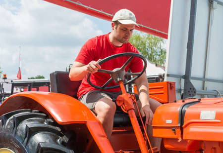 agriculture machinery: Young farmer in Agricultural Fair