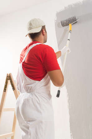 wall paint: Young Man On Painting Wall With Roller Stock Photo