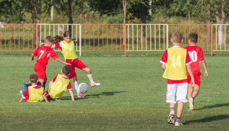 niñas jugando: Niños patadas de fútbol en el campo de deportes Foto de archivo