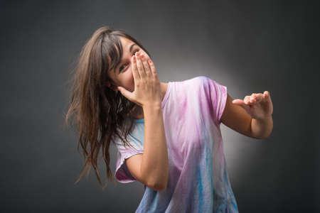 hand over: Young woman with hand over mouth Stock Photo