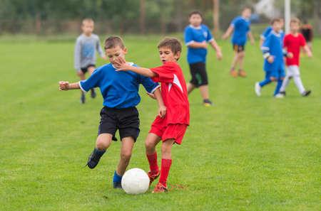 pelota de futbol: muchachos patadas de fútbol en el campo de deportes