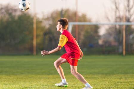 terrain de foot: Enfant jouant au football sur un terrain de football Banque d'images