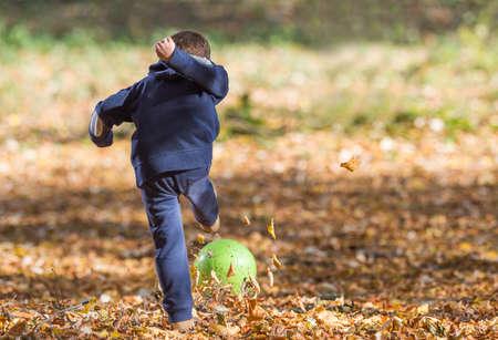 yellov: boy kicking ball in autumn leaves Stock Photo