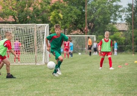 kicking: boy kicking football on the sports field Stock Photo