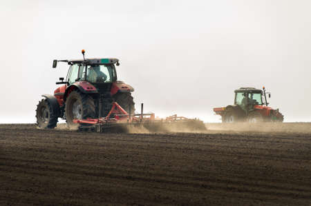 plough machine: Tractors preparing land for sowing