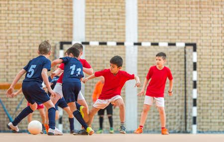 Little Boys playing soccer in indoors Foto de archivo