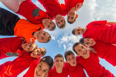 circulo de personas: niños del equipo de fútbol en el montón