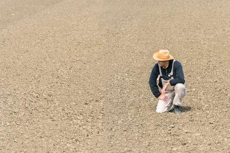 young farmer: young farmer watching plowed field