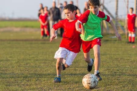 little boys: boys kicking football on the sports field