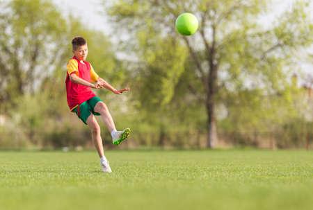 kicking: kid kicking a soccer ball on the field