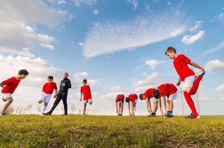 子供のサッカー チームがサッカーのフィールドで練習します。 写真素材