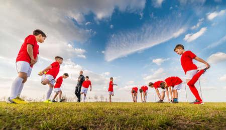 축구장에서 어린이 축구 팀 연습 스톡 콘텐츠