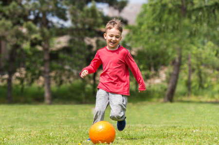 boy ball: Boy kicking ball in the grass outdoors
