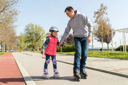 rollerskating: father teaching little daugther to roller skate