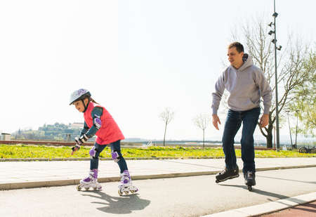 daugther: father teaching little daugther to roller skate