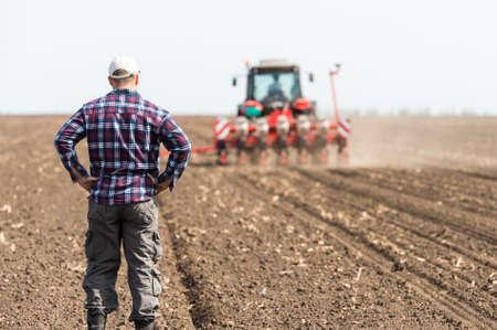 joven agricultor en tierras de labranza con tractor en el fondo