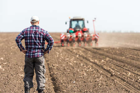młody rolnik na użytki rolne z ciągnika w tle