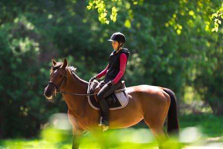 Mujer joven en un paseo a caballo en un bosque