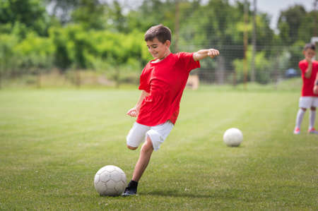 boys playing: Little Boy Shooting at Goal Stock Photo