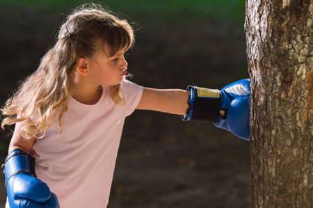 Little girl wearing blue boxing gloves