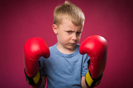 boy boxing: Little boy wearing red boxing gloves Stock Photo