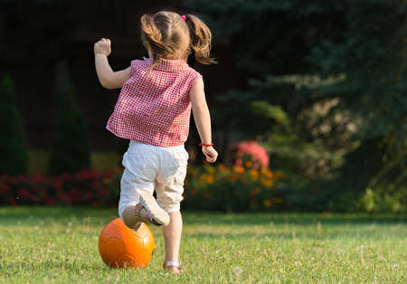 girl kick: Little girl Shooting at Goal Stock Photo