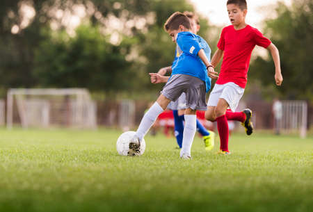 soccer ball on grass: Young boys playing football soccer game on sports field Stock Photo