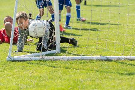 boys playing: Young boys playing football soccer game on sports field Stock Photo
