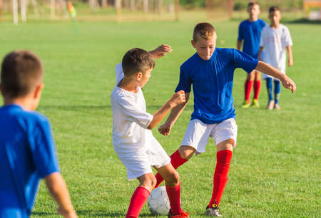 young boys: Young boys playing football soccer game on sports field Stock Photo