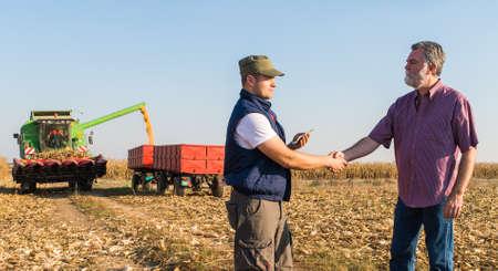 옥수수의 수확 후 행복한 농부가
