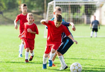 kinder spielen: Jungen kicking Fußball auf dem Sportplatz Lizenzfreie Bilder