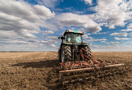Tractor preparing land for sowing Stock Photo