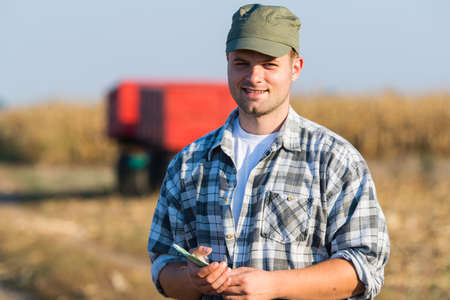 Happy young farmer after harvest of corn