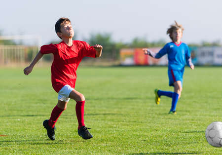 Young boys playing football soccer game on sports field Stock Photo