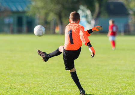 Young boy goalkeeper defends the goal