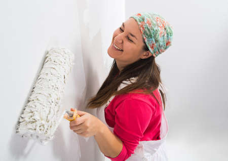eastern european ethnicity: Happy pretty young woman painting a wall