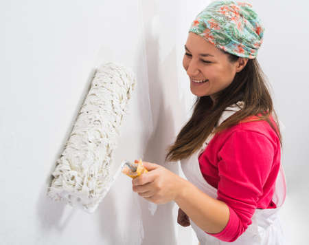 Happy pretty young woman painting a wall