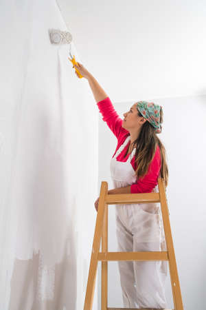 eastern european ethnicity: Young pretty girl standing on a ladder painting the walls Stock Photo
