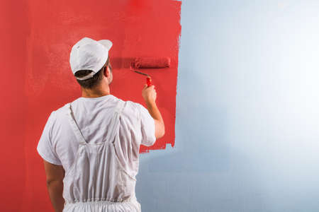 hombre rojo: pared de pintura joven hombre con el rodillo Foto de archivo